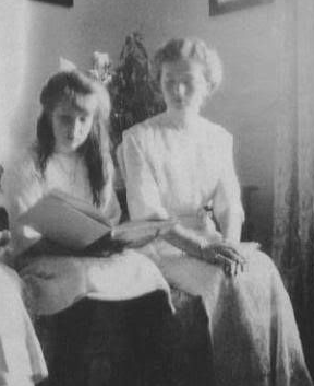 Grand Duchess Olga and Grand Duchess Anastasia looking at the Romanov family photo album.