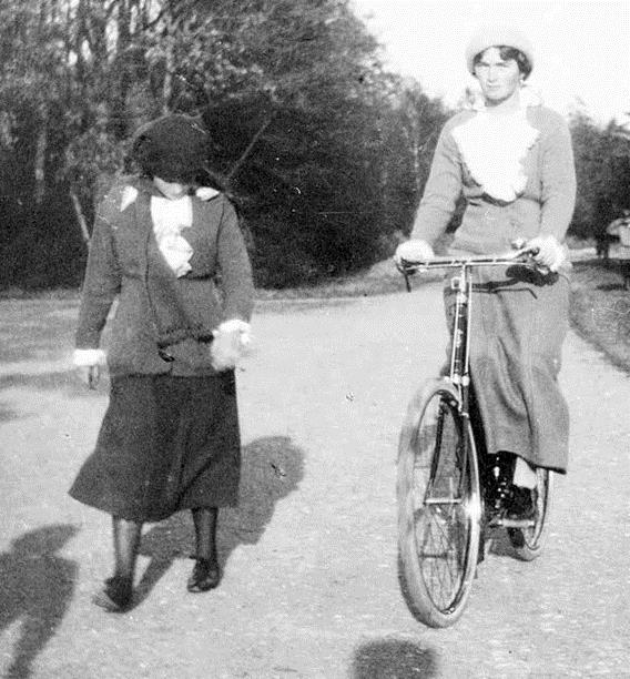 Grand Duchess Olga riding her bike and Grand Duchess Anastasia next to her on foot.