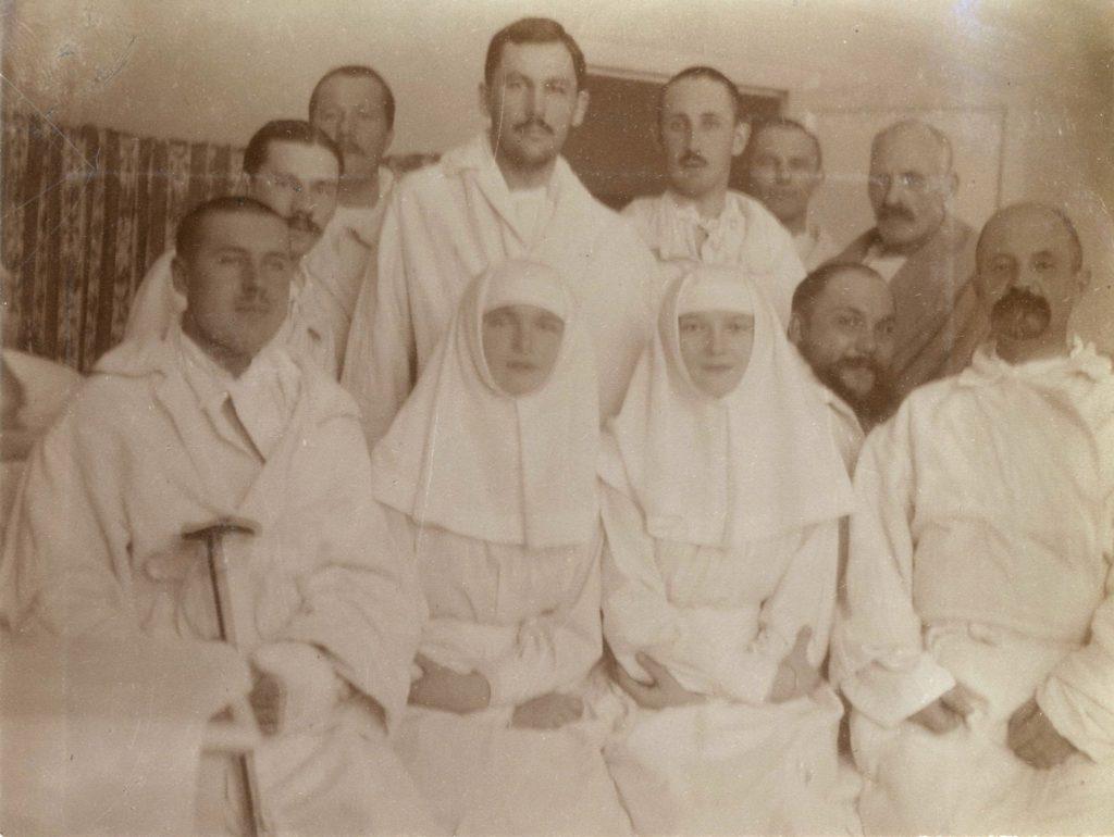 Sister Olga Romanov and Sister Tatiana Romanov posing with the wounded at their Tsarskoe Selo infirmary in 1915.